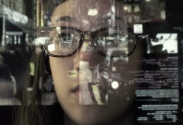 An asian woman concentrating on a touch screen display. The point of view is from behind the screen, looking through the data and images to the woman's face as she manipulates the windows of information.
