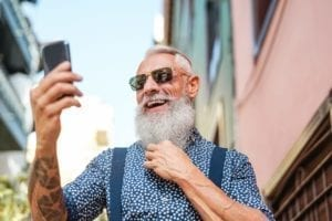 Bearded senior using mobile phone outdoors