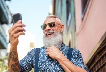 Bearded senior using mobile phone outdoors
