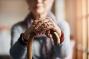 Cropped shot of a senior woman holding a cane in a retirement home