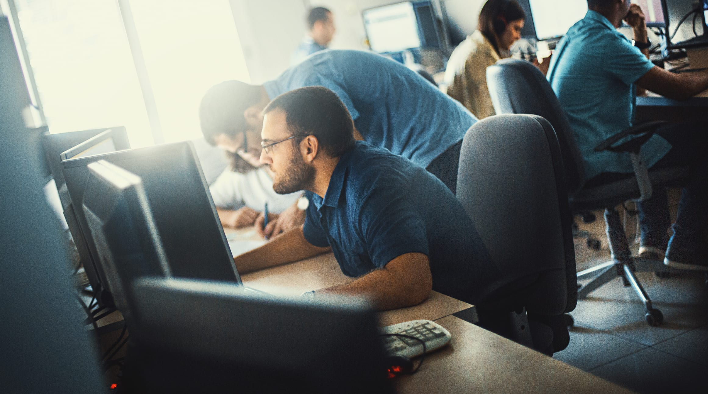 Group of mid 20's and 30's men and women engaged in application development job. They are seated by long desks back to back, each person in front of dual screen computer.