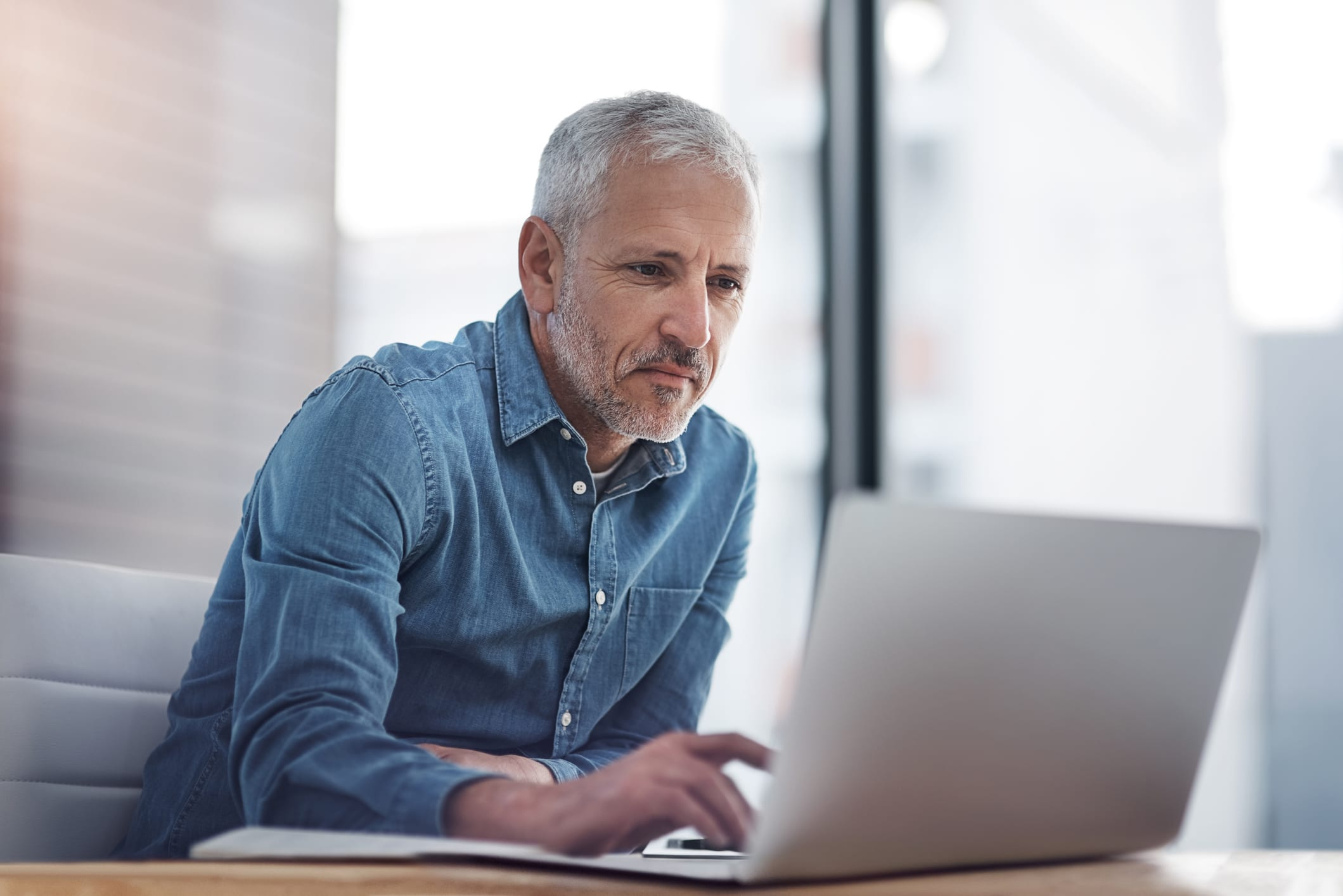 Cropped shot of a mature businessman working on a laptop in an office