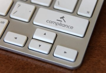 Close up of a keyboard, but instead of a shift key, there is a compliance key