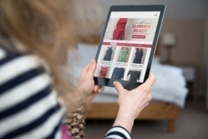 A woman is shopping on a digital tablet on a shopping website.