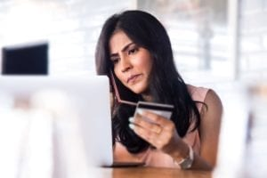 A woman on her phone in front of a laptop. She holds her credit card and looks upset.