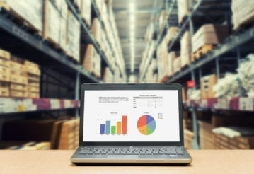 Laptop with analysis of sales onscreen, on a table with blurred warehouse cargo in the background.