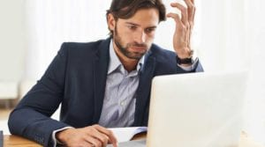 Frustrated business man looks at his laptop