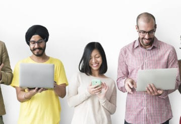 Smiling young adults standing in a line looking at their electronic devices.