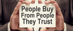 "Hands holding sign that says ""People buy from people they trust"""