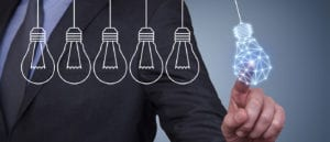 Suited man touches a graphic of a stylized lightbulb