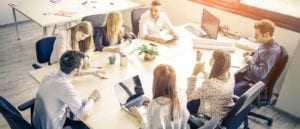 Young business people around a boardroom table