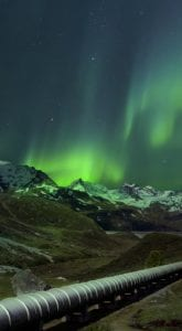 Aurora Borealis over mountains and a gas pipeline