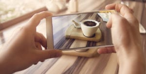 Hands holding a mobile phone, taking a picture of a latte on a wooden board.