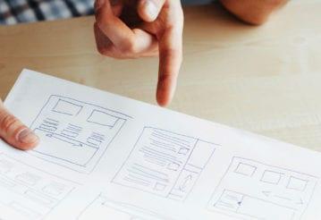 A man's hands hold drawn mock ups of a website design