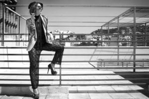 Monochrome image of a fashionable woman smoking outside