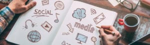 An open sketch book on a table with social media related illustrations.