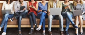 Cropped image of people sitting down and looking at their electronic devices.