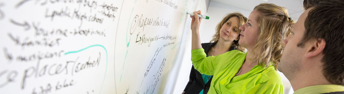 Woman writing on a whiteboard with a co-worker on either side.