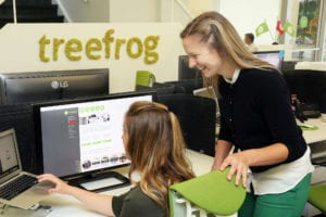 Two women work over a computer in the Treefrog office