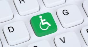 Close up of a computer keyboard, but one key is green with a wheelchair symbol.
