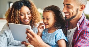 A smiling family looks at a computer tablet