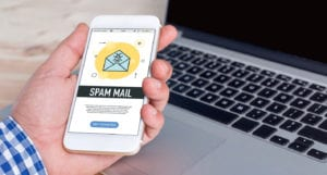 Man's hand holding a mobile phone displaying a spam mail graphic