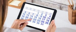 A woman holds a computer tablet displaying a calendar