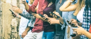 Cropped image of various people holding their mobile phones