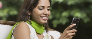 Smiling woman in a green scarf holds and looks at her mobile phone.