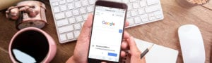 Hand holding a mobile phone displaying the Google search homepage