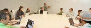 Several Treefrog employees around a conference table watching a man draw on a whiteboard.