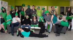 A group of Treefrog employees wearing a variety of green accessories