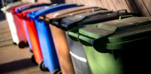 Series of different coloured garbage bins lined up outdoors