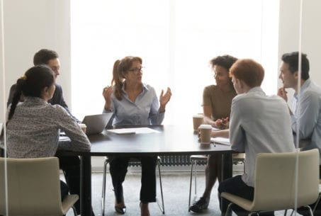 Female executive talking to coworkers at a corporate briefing, sitting at a conference table in a boardroom