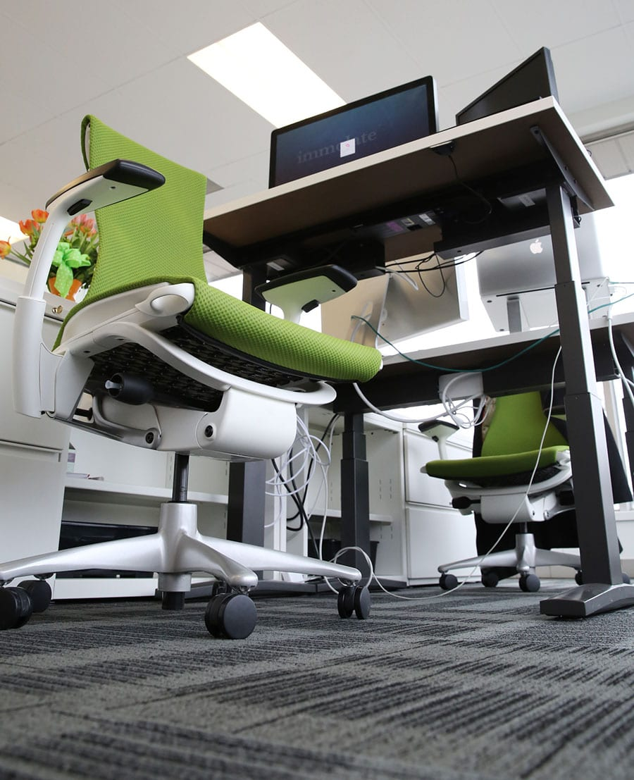 A photo of a green office chair by a desk taken from floor level