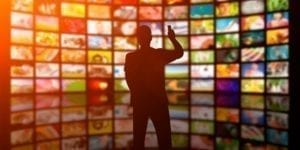 silhouette of man standing in front of wall of tv screens