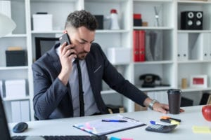 A business man holds a cell phone to his ear while sitting at at desk.