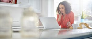 A curly haired woman in a red shirt talks on the phone while sitting in front of a laptop