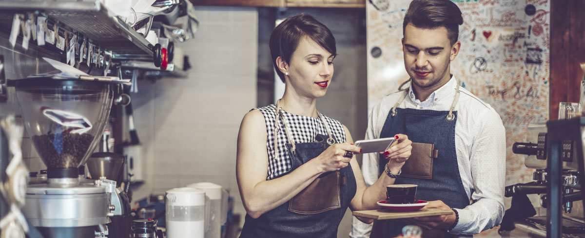 Two restaurant workers take mobile photo of latte