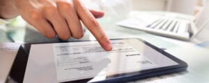 Close-up Of A Businessperson's Hand Analyzing Bill On Digital Tablet Over Desk