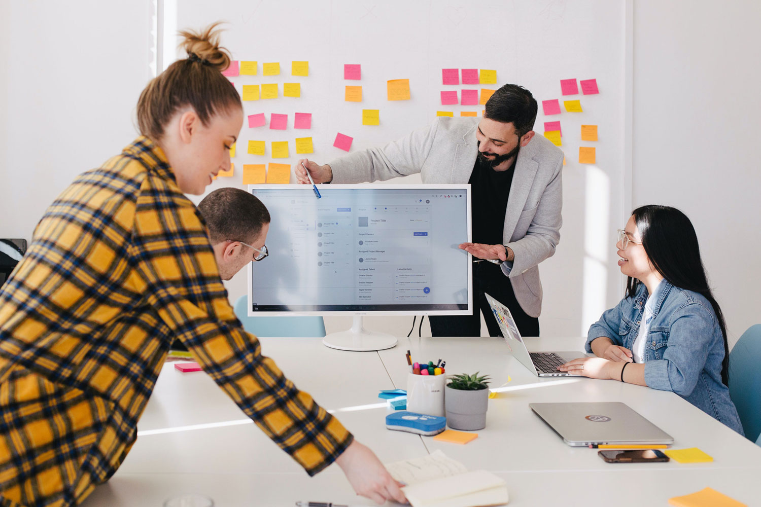 group of office workers at conference table. Post-its cover the wall in behind them